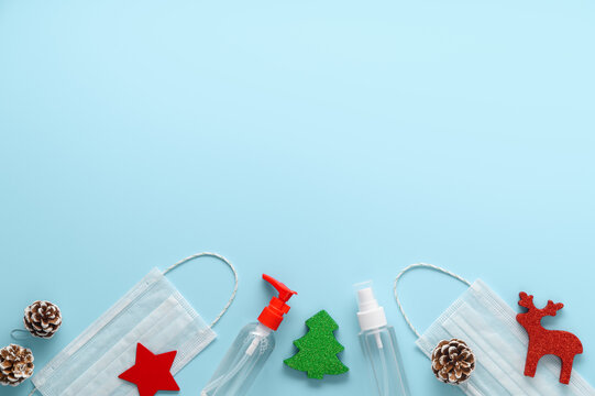 Christmas era covid concept. Top view of Medical protective masks, sanitizer bottles and Christmas decorations on pastel blue background. Layout, copy space. Coronavirus