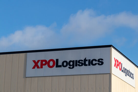 Red and black XPO Logistics logo on white background on warehouse
