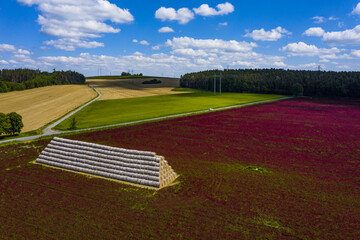 Crimson clover field and heap of bales from above