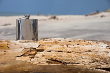 Hip flask on a wooden beam lying on the beach.