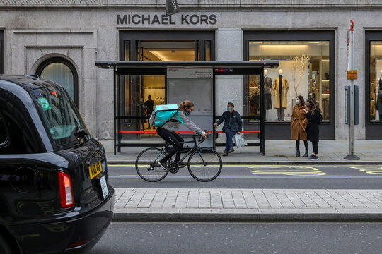 A taxi passes a Deliveroo rider as people wait at a bus stop in Regent Street