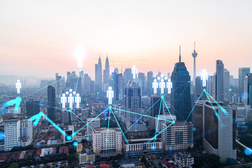 Hologram of social media icons over sunset panoramic cityscape of Kuala Lumpur, Malaysia, Asia. The concept of people connections in KL. Multi exposure.