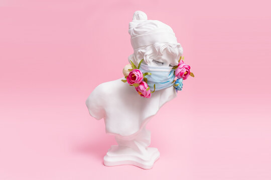 Sculpture of antique girl made of plaster in medical mask with flowers against coronavirus pandemic and common cold. Beauty salon fashion in pink background concept