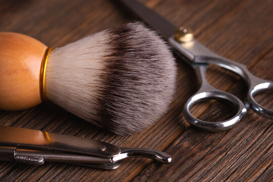 Shaving brush, razor and scissors. Close up barber tools on wooden background.