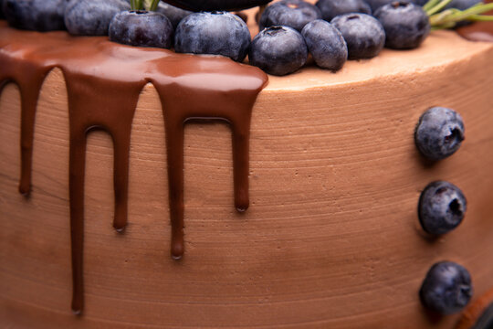 Drops of chocolate dripping down the cake. Handmade chocolate cake. Chocolate and blueberries close-up. Chocolate cake.