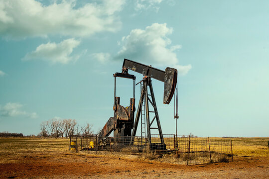Rusty oil well pump jack  sitting in winter pasture with rough hay stubble and clay covered ground and bare trees on horizon under pretty blue sky