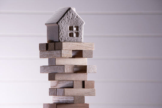 wood block with model  house on wood block game. Investment risk and uncertainty in the real estate housing mark.