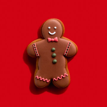 Homemade cookie. Bakery food art. Festive sweet ornament. Brown happy smiling gingerbread man shape biscuit with chocolate icing decor isolated on red background.