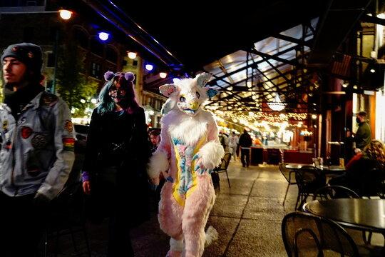 People in Halloween costumes walk through Milwaukee's Historic Third Ward neighborhood