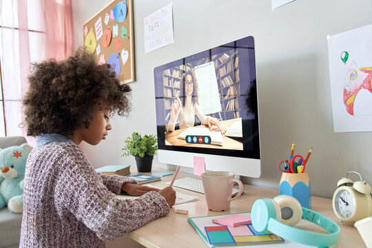 Cute smart african primary school kid girl distance learning by video conference call chat with remote teacher, online tutor teaching digital class, web lesson on computer at home. Virtual education.