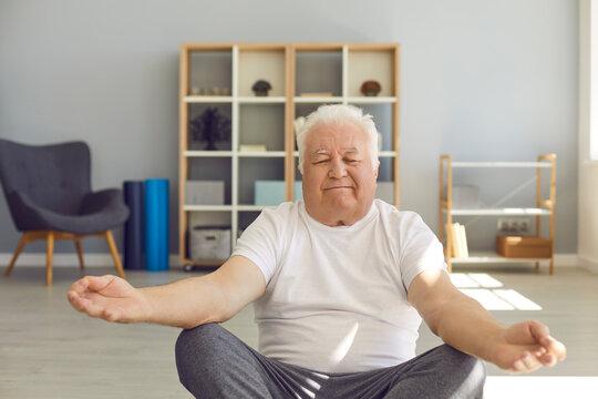Senior man doing yoga, meditating and practising breathing exercise at home or in wellness center