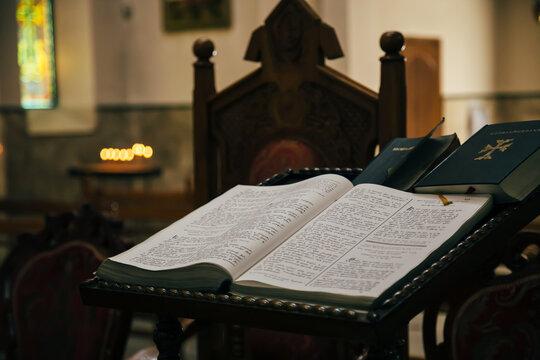 The open Bible in armenian language lying in the empty dark Armenian Church