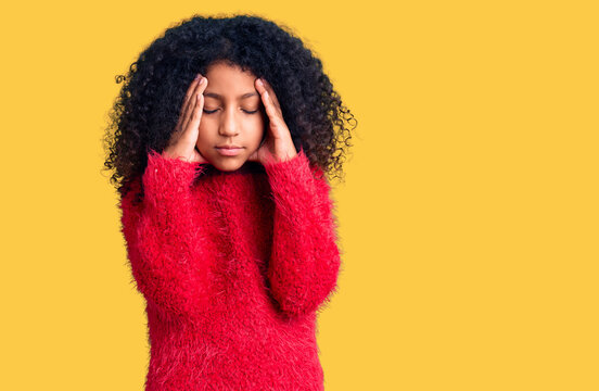 African american child with curly hair wearing casual winter sweater suffering from headache desperate and stressed because pain and migraine. hands on head.