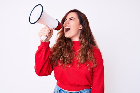 Young beautiful brunette woman screaming using megaphone over isolated white background