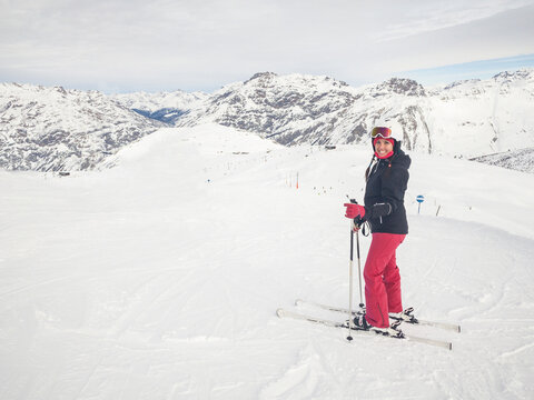 Happy woman with ski on top of mountain slopes - Beautiful young woman enjoying ski holidays and having fun on the snow on a beautiful sunny winter day in Livigno - Sport and travel concepts