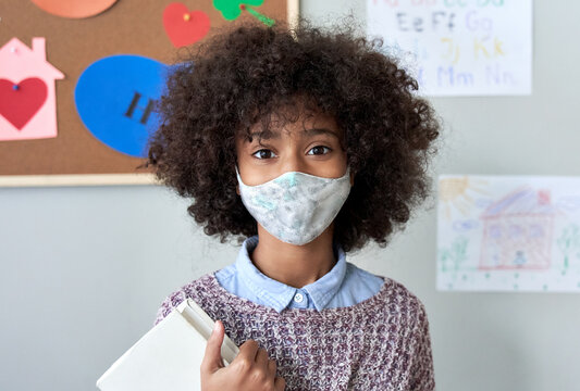 Cute small elementary reopen school pupil african american kid child girl wearing face mask looking at camera standing in classroom. Children safety for covid protection, headshot close up portrait.