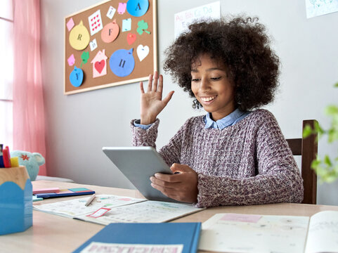 Happy african american mixed race kid girl waving hand talking with remote web teacher on social distance video conference call elearning virtual class on tablet. Children learning at home concept.
