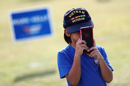 A child holds a telephone during an event in support of Democratic U.S. presidential nominee Joe Biden at a public park in Phoenix, Arizona