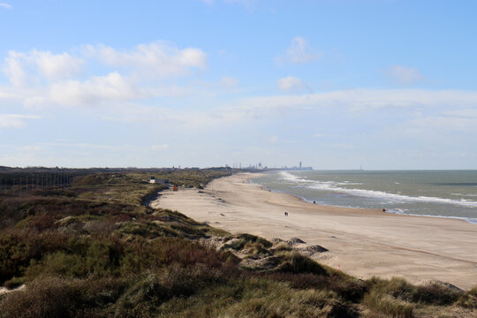 Strandspaziergänger und Strandgras am Nordseestrand bei De Haan, Flandern, Belgien