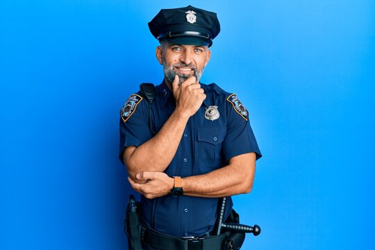 Middle age handsome man wearing police uniform looking confident at the camera smiling with crossed arms and hand raised on chin. thinking positive.