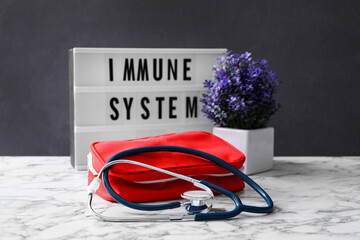 Lightbox with words Immune System, flowers and first aid kit on white marble table Fototapete