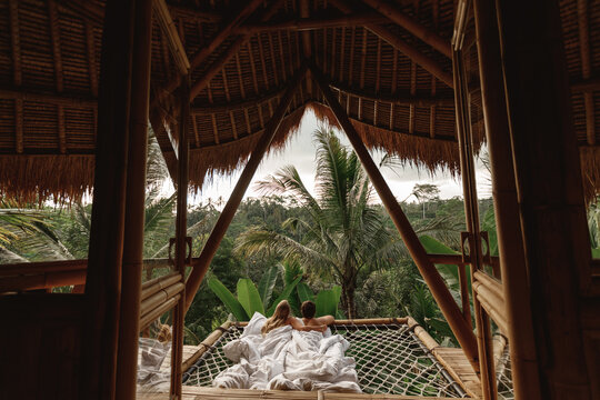 Young caucasian travel couple lie  in hammock in  bamboo eco house, nature and mountains on background. Morning in tropical resort on Bai island