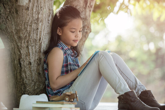 little asian girl reading a book under big tree with hat, book, and model plane beside. children and science. blurred background. learning the imagination and dreams of rural child. studying at home.