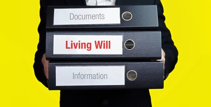 Living Will. Man carries stack of folders. File folders with text label. Background yellow.