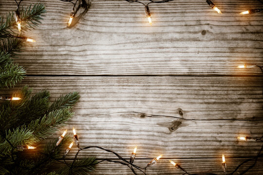 Christmas background - Christmas lights bulb and  fir branch on rustic wood table, frame border design. Merry Christmas and New Year holiday background. top view.
