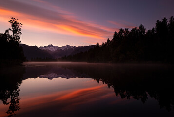 Snow-capped Mount Cook and Mount Tasman reflected in lake Matheson at Sunrise, South Island, New Zealand