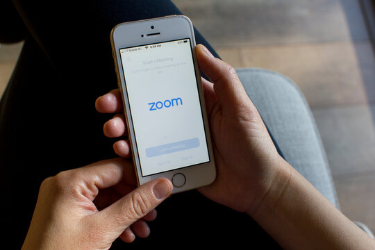 Portland, OR, USA - Mar 15, 2020: A woman opening the Zoom mobile app on her smartphone. Zoom users can opt to record sessions, collaborate on projects, and share or annotate on one another's screens.