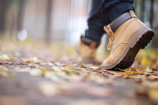 Autumn concept. Pedestrian feet on the road. Autumn leaves on the footpath.