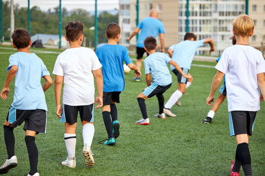 training and football match between youth soccer teams in stadium, boys have hard competition, running and kicking soccer ball