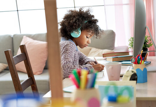 Smart serious african american school kid girl wearing headphones virtual distance learning online listening remote language digital class doing homework studying at home sit at desk with computer.
