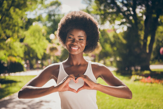 Photo portrait of woman making heart with hands outdoors