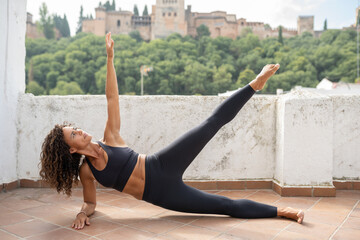 Middle-aged woman with fitness body working out on the terrace of her house Wall mural