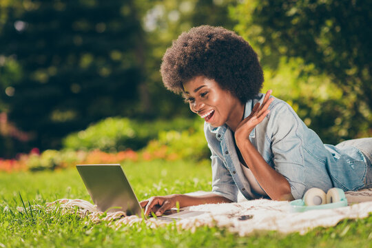 Side profile photo of black skinned young female student lying on grass working with computer web conversation joking laughing