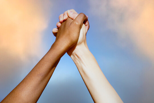 Multiethnic women's hands together against cloudy sky.