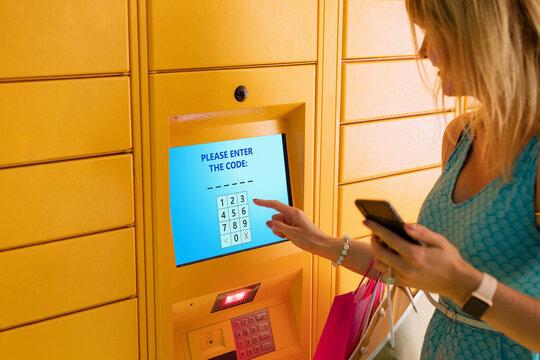 Woman entering code to receive parcel in post locker