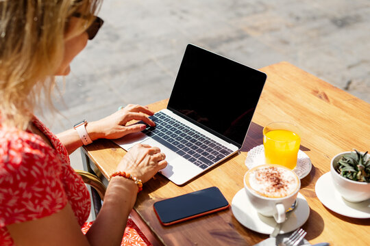 Woman working with laptop computer in outdoor cafe