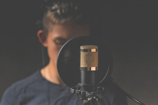 Studio microphone for sound recording. The singer in the background blurred background. Low key lighting