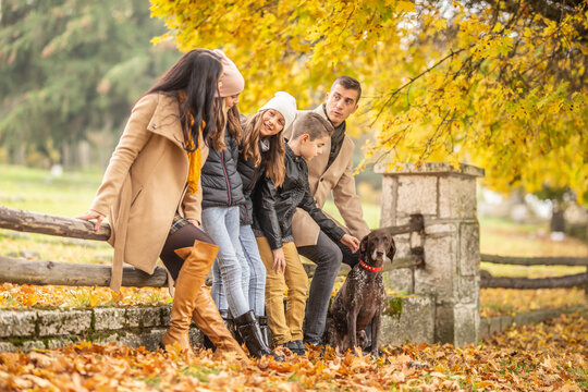 A family talks and enjoys moments outdoors during a colorful fall day