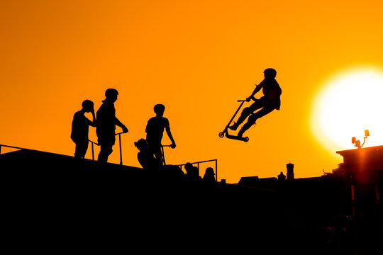 Unrecognizable teenage boy silhouette showing high jump tricks on scooter against orange sunset sky at skatepark. Sport, freestyle, extreme, youth, urban culture, outdoor activity concept