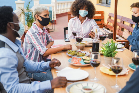 Young multiracial people eating and drinking together while wearing face protective masks - Focus on black girl