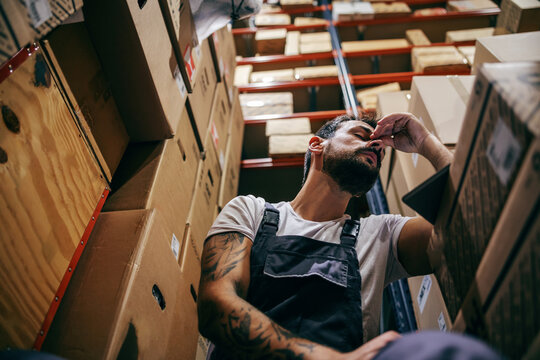 Tattooed bearded worker in overalls having hard day on the work. Storage of import and export firm interior.