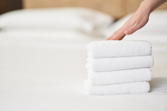 Female hand touching stack of fresh white bath towels on the bed