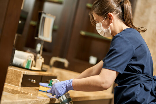 Housemaid in uniform and protective gloves cleaning the hotel bathroom