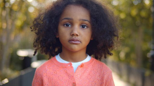 Close up portrait of serious little african girl looking at camera