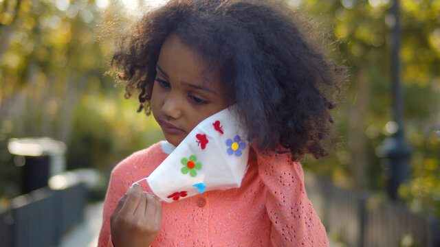 Portrait of little african girl putting on protective mask standing outdoors