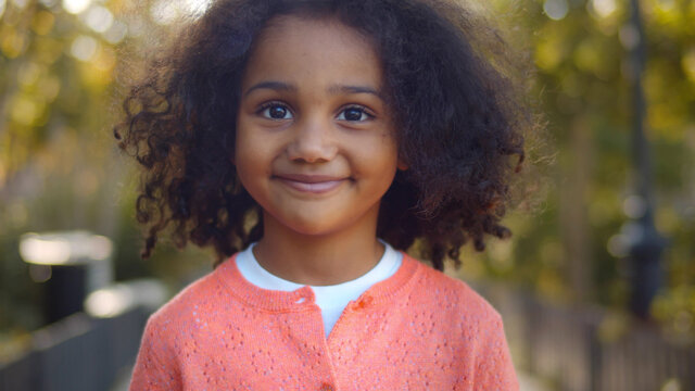 Close up of happy cute little african girl smiling at camera outdoors